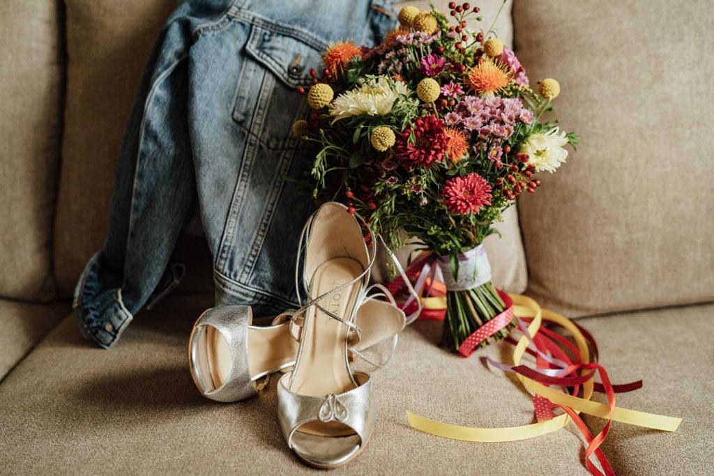 Detale ubioru Panny Młodej: srebrne buty do ślubu, kolczyki, jeansowa kurtka oraz bukiet z polnych kwiatów.