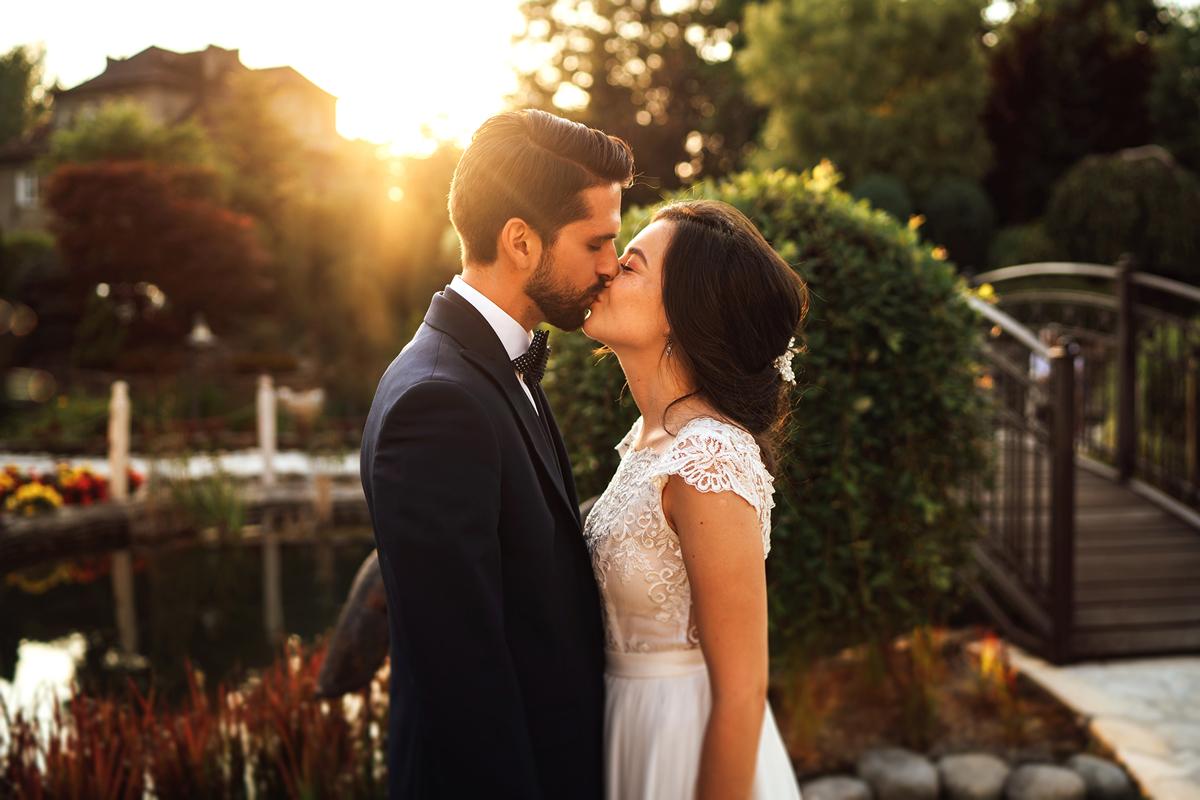 Fotografia ślubna Katowice, piękna panna młoda całująca pana młodego przy promieniach zachodzącego Słońca. Mini sesja w dniu ślubu.